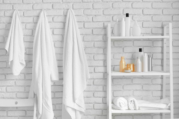 Bathroom shelving with cosmetic bottles and hanging towels against white brick wall