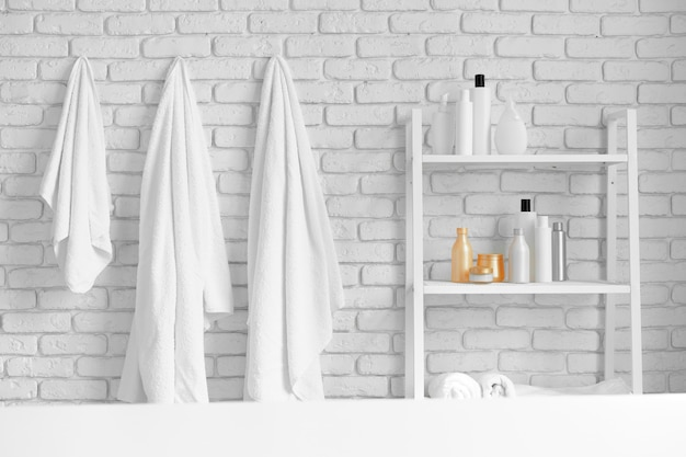 Bathroom shelving with cosmetic bottles and white hanging towels against white brick wall