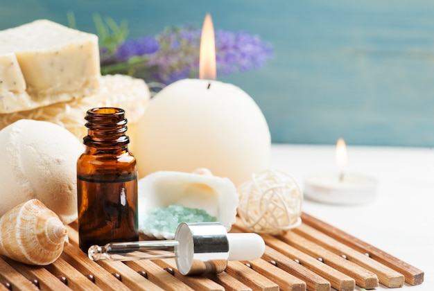 Bathroom spa set with essential oil, salt, bomb, nadmade soap and lit candles. concept for massage, relaxation and aromatherapy