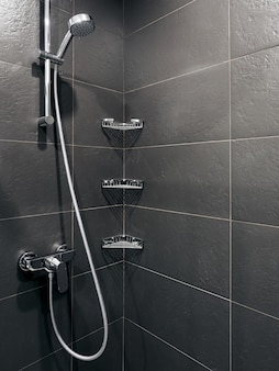 Bathroom toilet and shower in hotel with grey and white walls