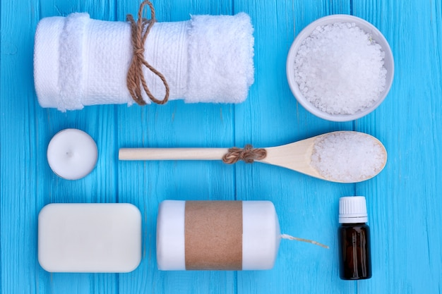 Bathroom towel with sea salt and soap flat lay top view. blue wooden desk background.