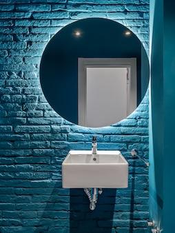 Bathroom with blue bricks wall, square wash basin and round mirror. minimalist interior.