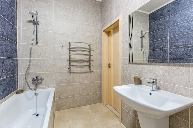 Bathroom with shower, bathtub and light tiles