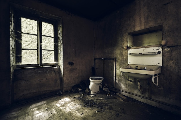 Bathroom with a sink on the wall covered in the dirt under the lights in an abandoned building
