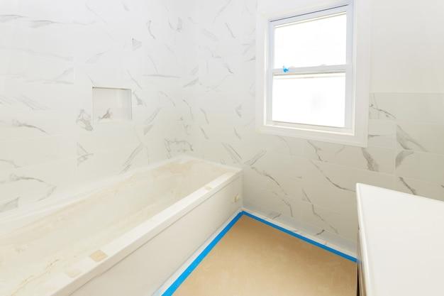 Ванная комната с плиточными стенами и полом с установленной душевой кабиной и раковиной находится в строящейся квартире дома.