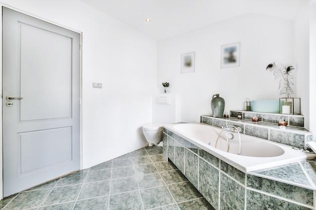 Ванна и душевая кабина расположены на плиточной стене возле шкафа с раковиной у окна в доме