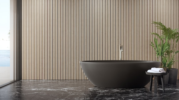 Bathtub on black marble floor of large bathroom in modern house