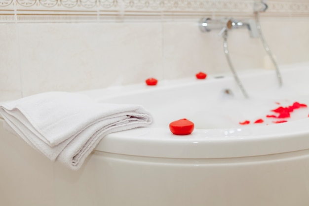 A bathtub filled with foam water and red rose petals. around the red and white candles.