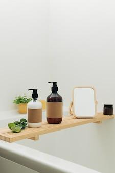 背景として白いタイルとモダンなインテリアスカンジナビアのバスルームに美容化粧品のボトルとアクセサリーを備えたバスタブ木製トレイ。キャンドルと緑の植物の家の装飾。