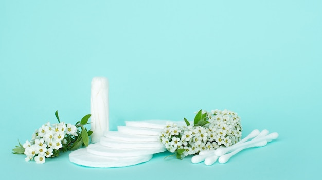 Batons and cotton buds for ears and makeup remover made of cotton on a turquoise background with small white flowers.