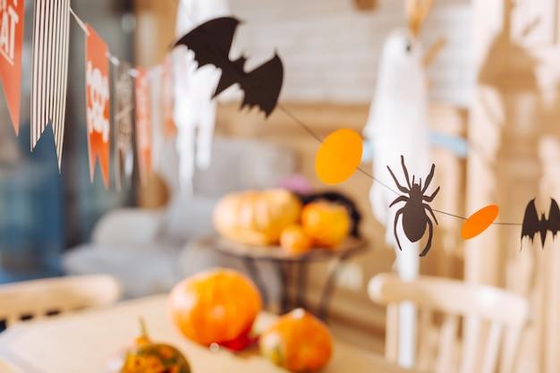 コウモリとクモ。小さな子供たちのハロウィーンの装飾として使用される紙で作られた小さなコウモリとクモ