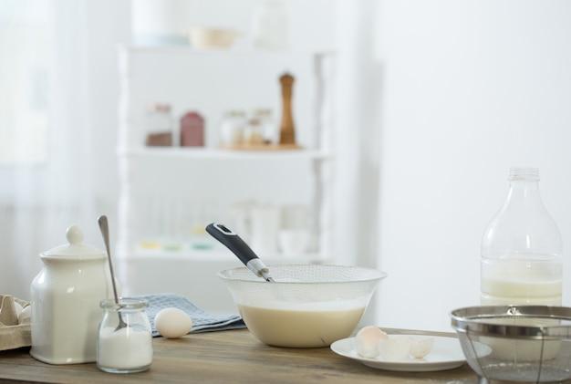 Тесто на деревянном столе в белой кухне
