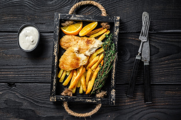 Battered fish and chips dish with french fries and tartar sauce in a wooden tray