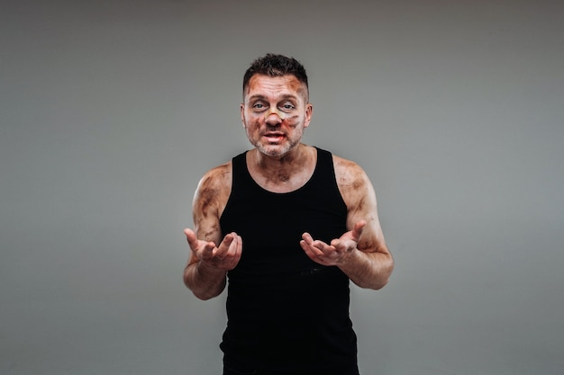 A battered man in a black t shirt who looks like a drug addict and a drunk stands against a gray background.
