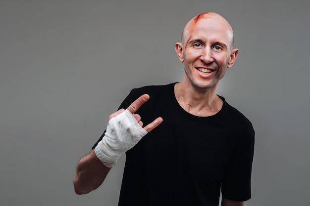 Избитый мужчина в черной футболке со скрученными руками
