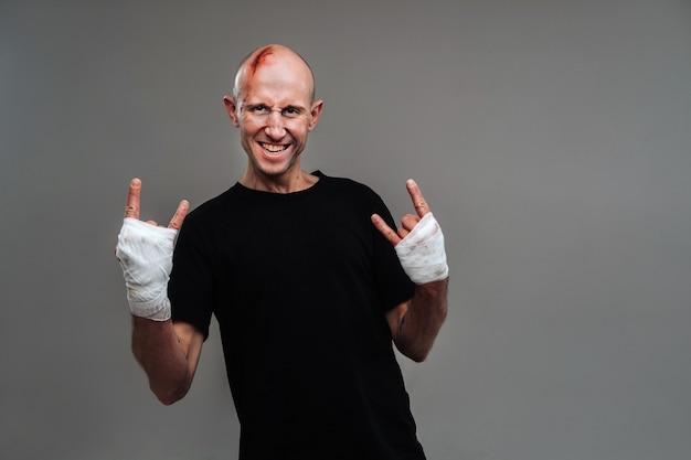 Избитый мужчина в черной футболке со скрученными руками Premium Фотографии