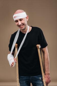 包帯を巻いた頭と腕にギプスをつけたボロボロの男が松葉杖の上に立っている