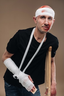 A battered man with a bandaged head and a cast on his arm stands on crutches on a gray background
