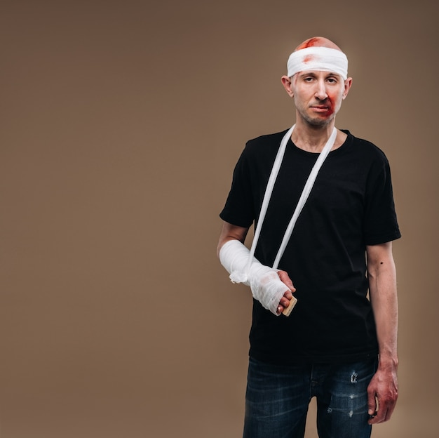 A battered man with a bandaged head and a cast on his arm stands on crutches on a gray background.