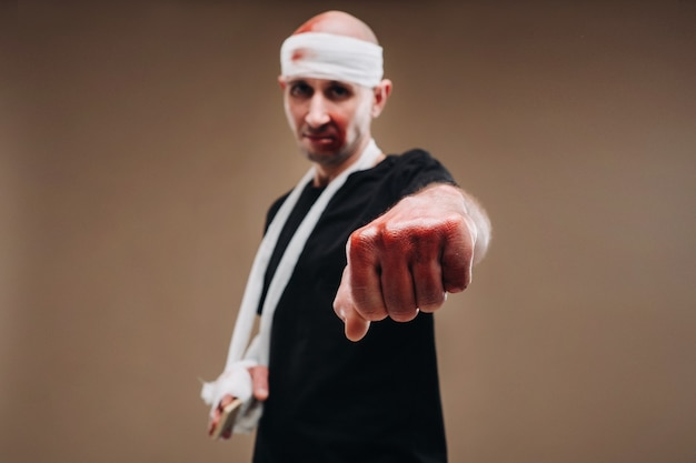 A battered man with a bandaged head and a cast on his arm stands on a gray background