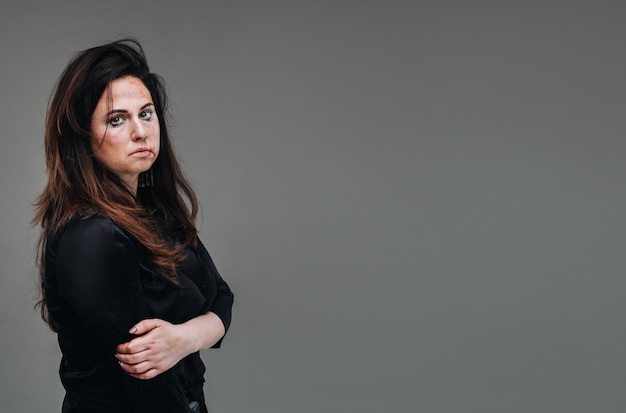 A battered woman in black clothes on an isolated gray background. violence against women.