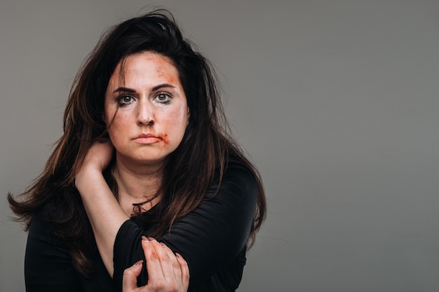 A battered woman in black clothes on an isolated gray surface. violence against women.