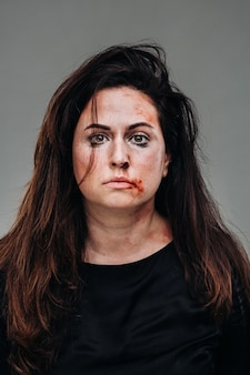 A battered woman in black clothes on an isolated gray wall. violence against women.