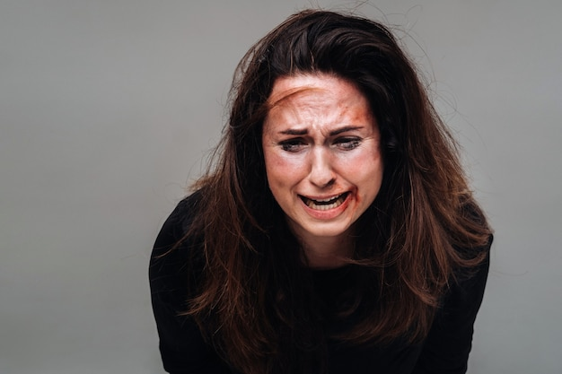 Battered woman in black clothes isolated