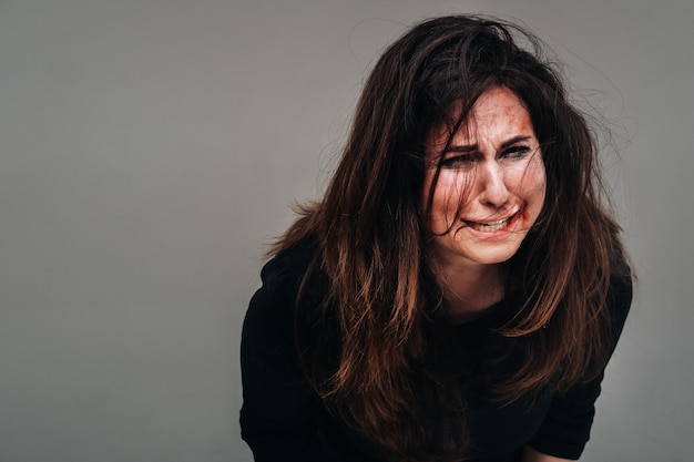 A battered woman in black clothes screams against an isolated gray background. violence against women.