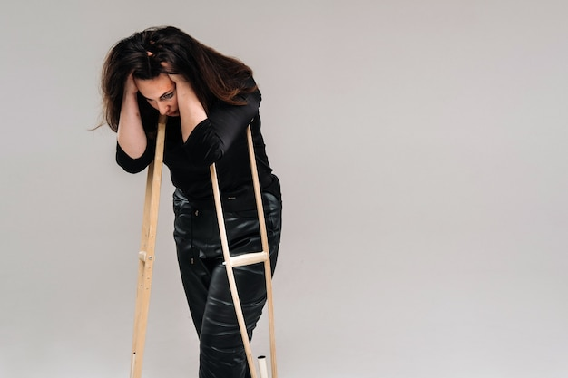 A battered woman in black clothes with casters in her hands on a gray background.