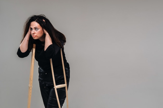 A battered woman in black clothes with casters in her hands on a gray background