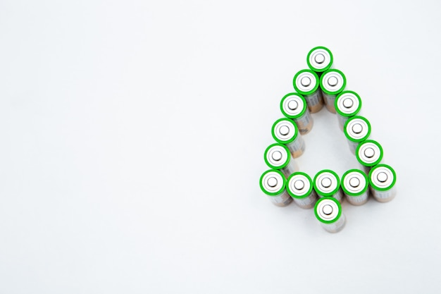 The batteries are in the shape of a christmas tree on a white background top view flat lay copy spac...