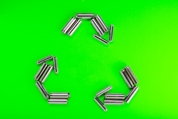 Batteries in the form of recycling on a green background. battery recycling, environmental.
