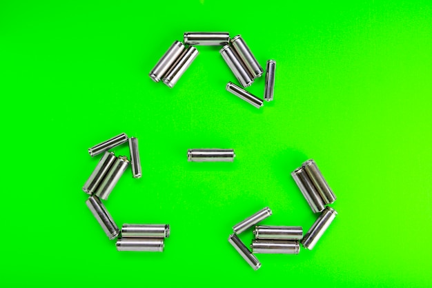 Batteries in the form of recycling on green. battery recycling, environmental concept.