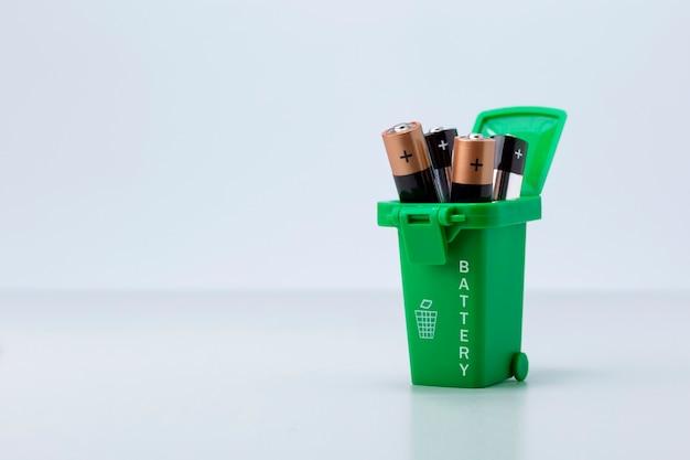 Батареи в зеленой корзине для мусора на белом сером фоне с копией пространства.