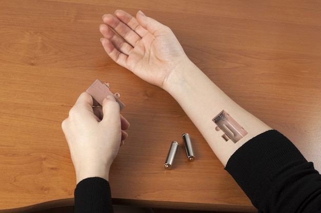 Batteries inserted into a hand.