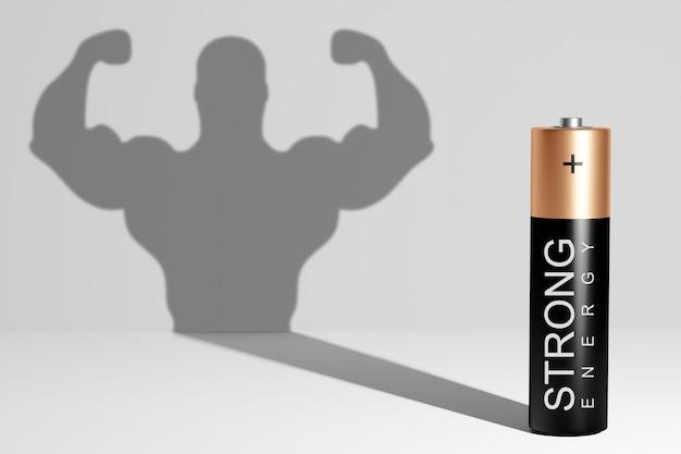 배터리는 크고 강한 근육질 남자의 그림자를 드리 우며 회색 배경에 그의 팔뚝을 보여줍니다. 내면의 힘. 리더십 능력. 고용량, 강력한 에너지.