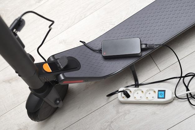 灰色の電動スタンドアップスクーターのバッテリー充電プロセス。