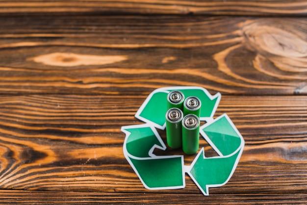 木製のテクスチャの背景にリサイクルアイコンのバッテリー