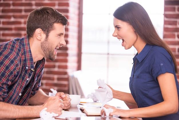남녀의 대결. 화난 남자와 여자가 사무실 테이블에 마주 앉아 서로 소리치는 측면 이미지