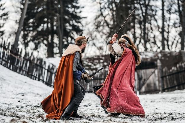 森と木製の要塞の近くの色のローブと帽子の2人の騎士の戦い。冬、雪の中で戦う騎士