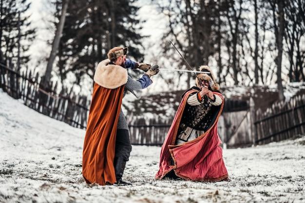 森と木製の要塞の近くの色のローブと帽子の2人の騎士の戦い。騎士は冬、雪の中で戦う