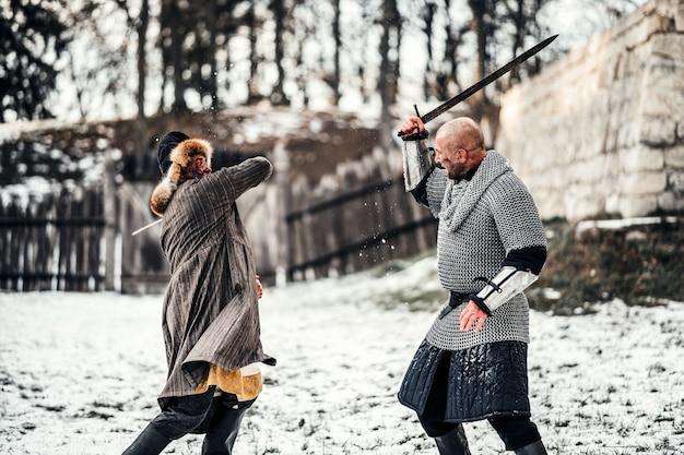 雪の中で剣と戦う武器を持つ鎧の2人の戦士の戦い