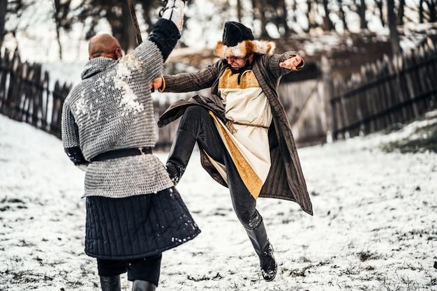 雪の中で剣と戦う武器を持つ鎧を着た2人の戦士の戦い