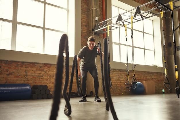 배틀 로프 연습. 체육관에서 밧줄로 crossfit 운동을 하는 젊고 강한 남자