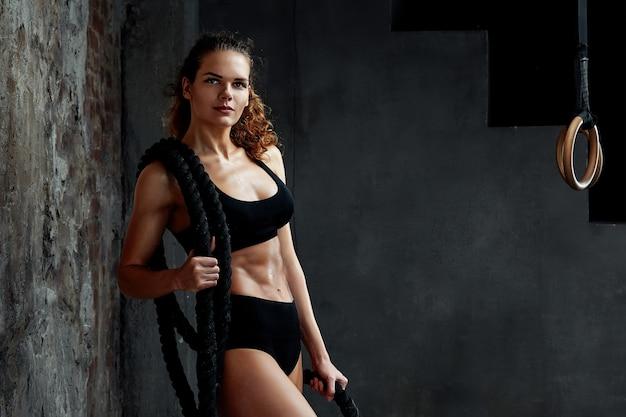 Сеанс боевых веревок. привлекательные молодые подходят и тонированное спортсменка, работающая в тренажерном зале фитнеса.