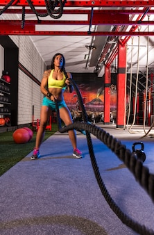 Battling ropes girl at gym workout exercise