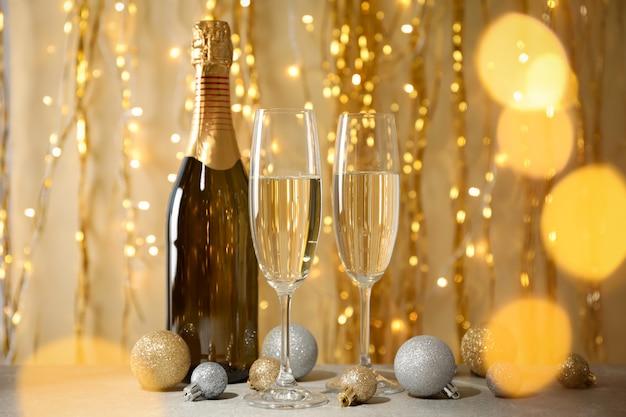 Фенечки, бокалы для шампанского и бутылка на фоне украшенного пространства. эффект боке