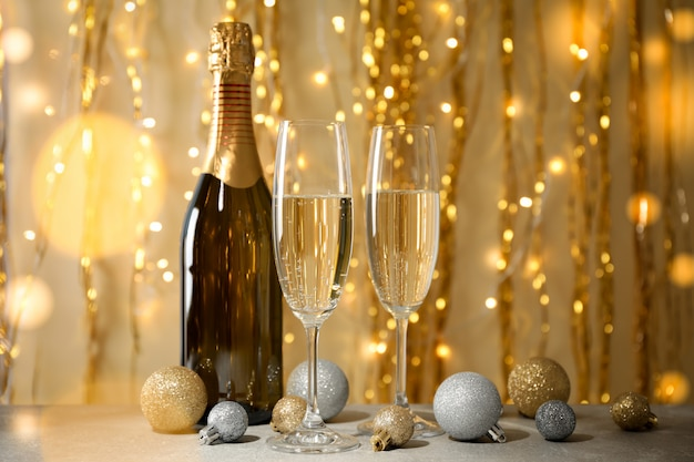 Baubles, champagne glasses and bottle against decorated space. bokeh effect