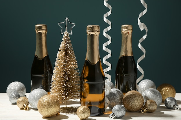Baubles and champagne mini bottles on white wooden table, close up